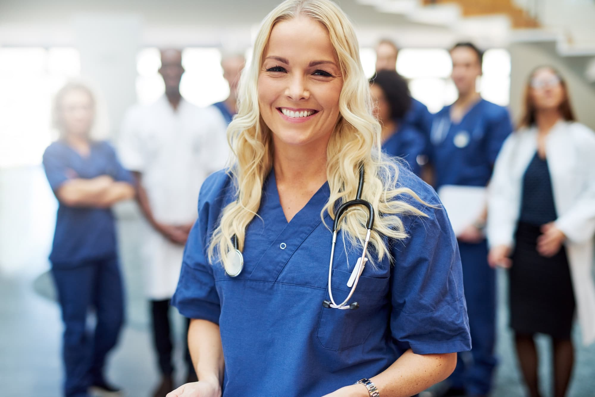 Smiling blond doctor with stethoscope in hospital
