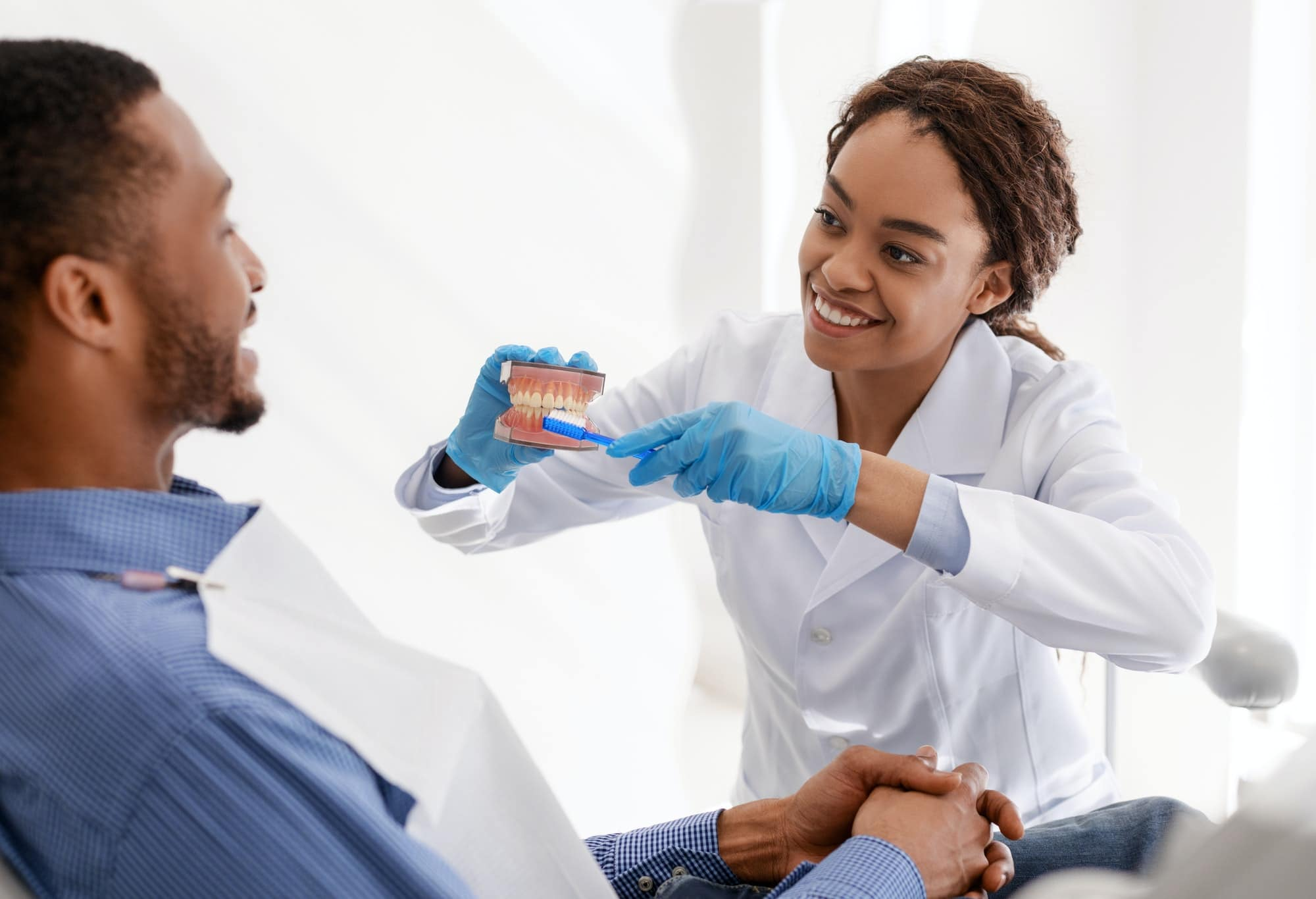 Dentist showing patient how to brush teeth in accurate way